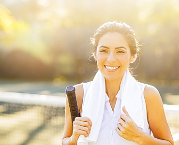 Portrait of smiling young woman with towel and tennis racket