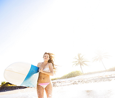 Young woman running in surf carrying surfboard, Jupiter, Florida