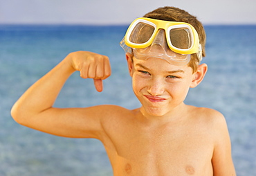Boy (10-11) wearing swimming goggles flexing muscles