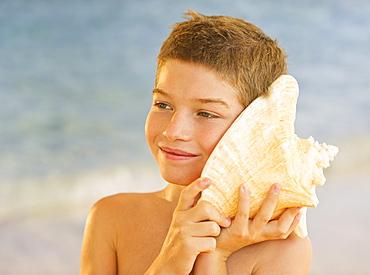 Boy (10-11) listening to sea shell on beach
