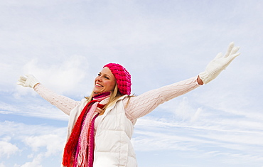 Woman in winter clothing raising arms