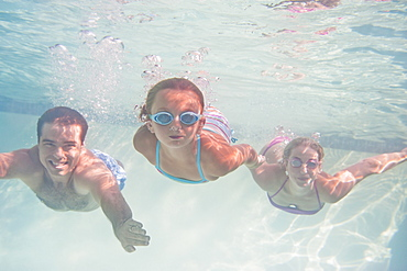 Parents with daughter (10-11) swimming underwater
