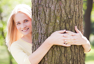 Woman embracing tree