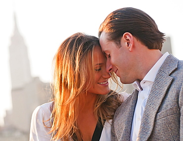 USA, New York, Long Island City, Close-up of happy young couple, Manhattan skyline in background