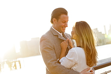 USA, New York, Long Island City, Young couple flirting on bridge, Manhattan skyline in background