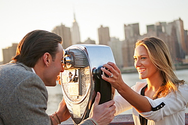USA, New York, Long Island City, Young couple looking through coin operated binoculars, Manhattan skyline in background