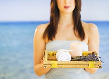 Young woman carrying tray with spa equipment, studio shot