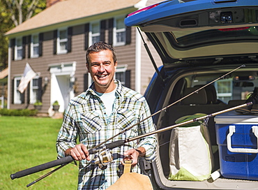 Portrait of man holding fishing rods in front of packed car, Mendham, New Jersey