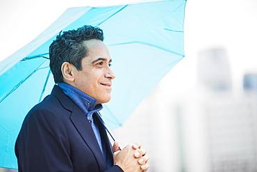 Portrait of man holding blue umbrella