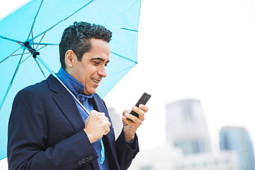 Portrait of man holding blue umbrella and using mobile phone