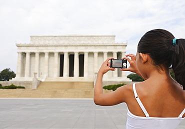 USA, Washington DC, girl (6-7) photographing Lincoln Memorial