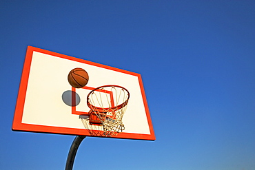 Basketball in mid air over hoop