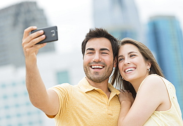 Couple taking self portrait photo with smartphone
