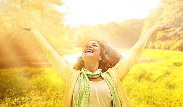 Woman reaching up to sunrays