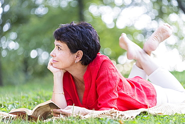 Mature woman lying on grass and reading book