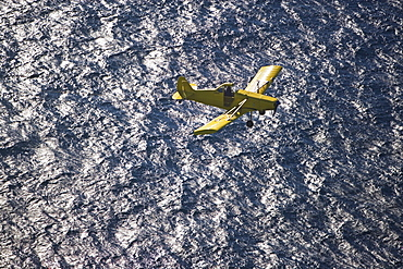 Small airplane ascending over water
