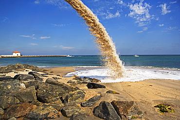 Pipe spraying sand on beach