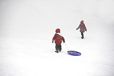 Kids pulling sled up snowy hill