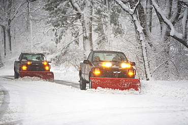 Trucks plowing snow off the road