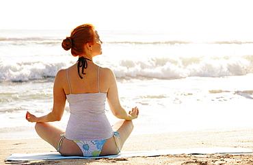 Woman practicing yoga on beach, Palm Beach, Florida