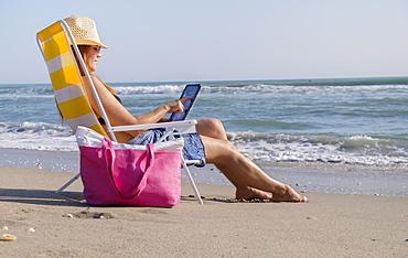 Woman sitting on deckchair and using laptop, Palm Beach, Florida