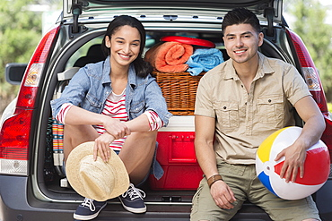 Portrait of young couple sitting in open car trunk