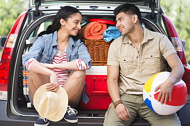 Young couple sitting in open car trunk