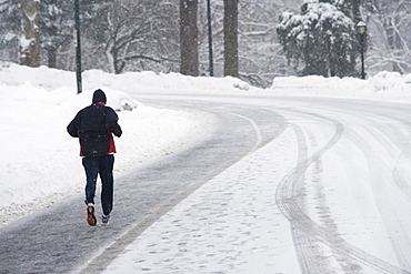 USA, New York City, man jogging up snowy road