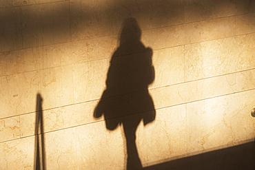 Shadow of female pedestrian on sunlit wall