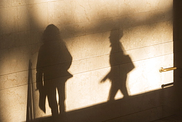 Shadow of two female pedestrians on sunlit wall