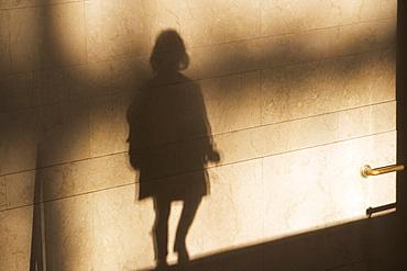 Shadow of single male pedestrian on sunlit wall