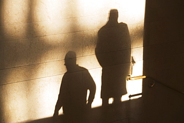 Shadow of two male pedestrians on sunlit wall