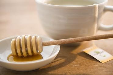 Studio shot of tea cup and honey spoon