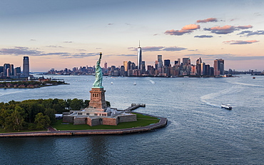 Aerial view of city with Statue of Liberty at sunset, New York City, New York