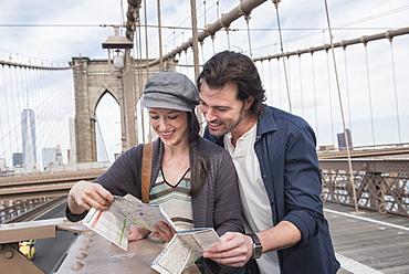 Happy couple reading map on Brooklyn Bridge, Brooklyn, New York