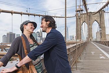Happy couple flirting on Brooklyn Bridge, Brooklyn, New York