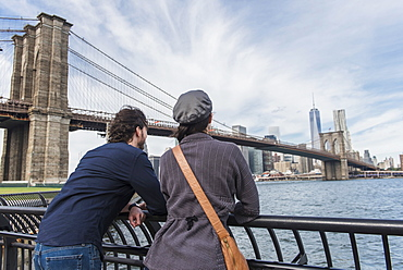 Couple leaning against railing and looking at Freedom Tower, Brooklyn, New York