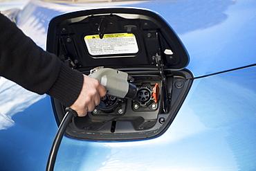 Close-up of man charging electric car