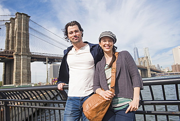Couple leaning against railing and looking at camera, Brooklyn, New York