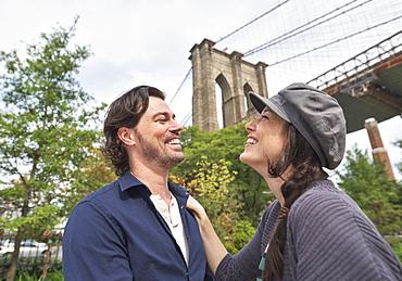 Happy couple standing against Brooklyn Bridge, Brooklyn, New York