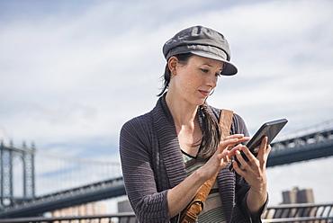 Woman using tablet pc, Manhattan Bridge in background, Brooklyn, New York