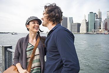 Happy couple standing against city skyline, Brooklyn, New York