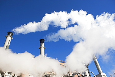 low angle view of factory chimneys