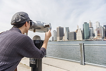 Woman watching cityscape through coin-operated binoculars, Brooklyn, New York