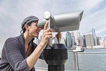 Woman watching through coin-operated binoculars, Brooklyn, New York