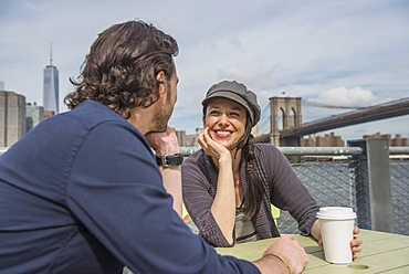 Happy couple sitting and discussing with cityscape in background, Brooklyn, New York