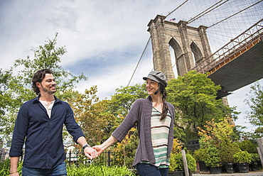 Happy couple holding hands and walking with Brooklyn Bridge in background, Brooklyn, New York