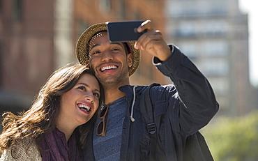 Couple taking selfie on street