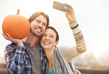Couple taking selfie with mobile phone, man holding pumpkin