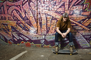 Young man with skateboard in front of graffitied wall